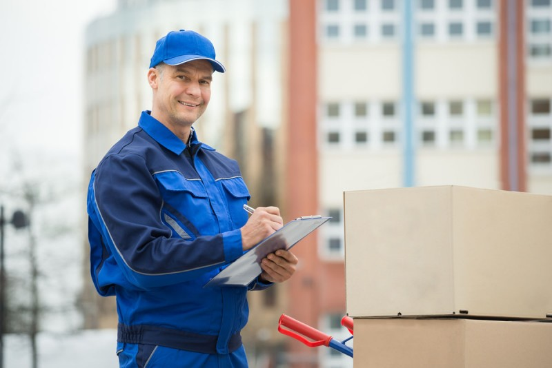 Portrait Of Delivery Man With Parcels And Clipboard