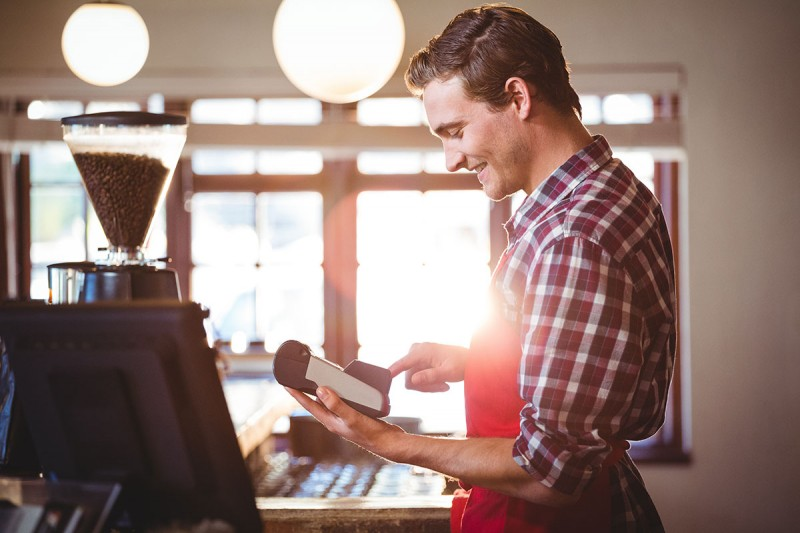 Smiling waiter using credit card machine