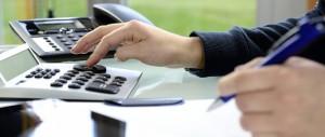 BannerFrau kalkuliert am Schreibtisch mit Taschenrechner